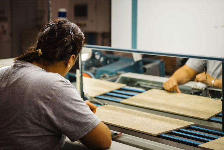 Addetta al controllo qualità in azienda ceramica che analizza una piastrella