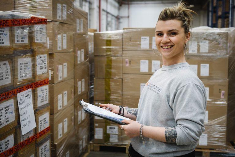 ragazza sorridente al lavoro in un magazzino di MM Operations
